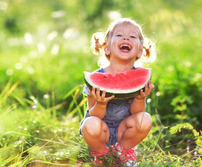 Mädchen lachend mit Melone